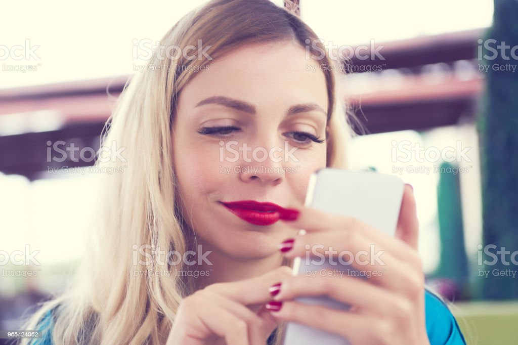 Happy Caucasian female watching on cell telephone screen while relaxing in cafe during free time royalty-free stock photo