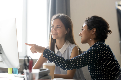 Happy Caucasian Intern Listening To Indian Mentor Explaining Computer Task Stock Photo - Download Image Now