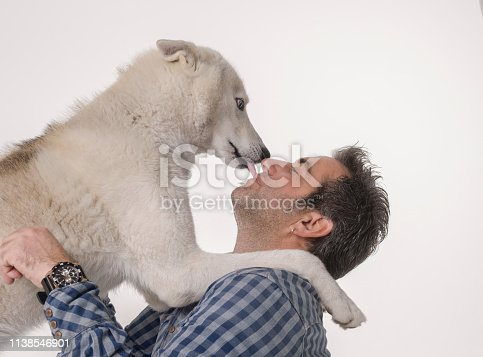 Happy caucasian man with husky dog over white background