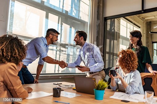 951514270 istock photo Happy caucasian manager and african client handshaking at group meeting 1204713980