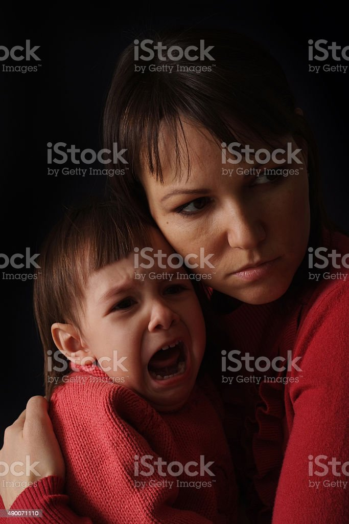 happy Caucasian mother with a sad crying daughter stock photo