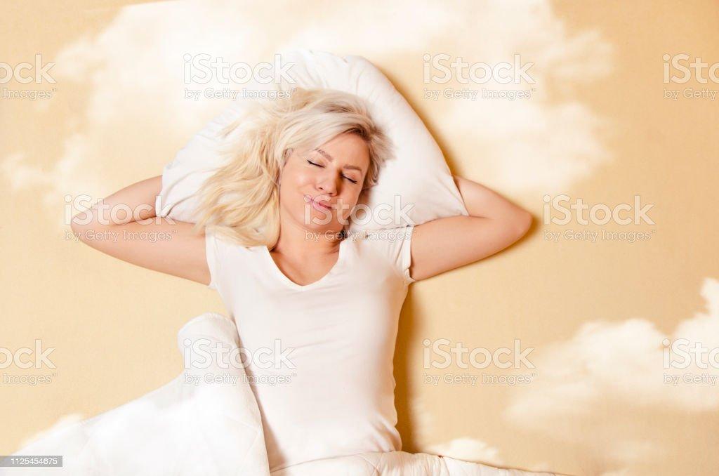 Happy Caucasian woman enjoying in good sleep, sleeping in clouds
