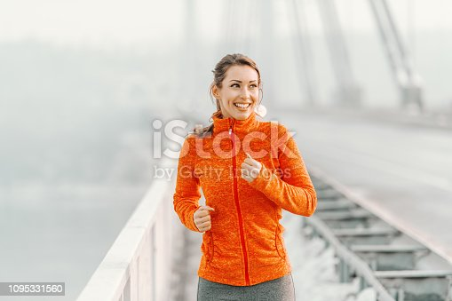 Happy Caucasian woman in sportswear and with ponytail running on the bridge at winter. Winter fitness concept.