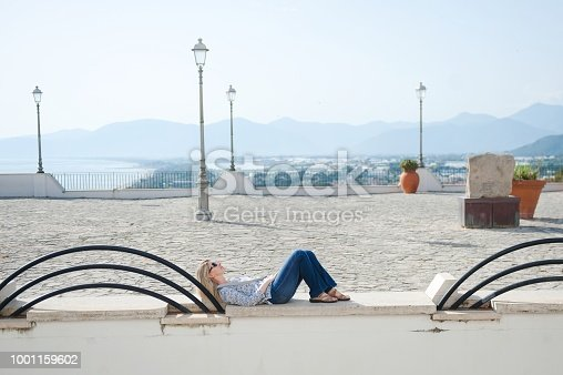 Happy Caucasian woman tourist is relaxing in Sperlonga, with background panoramic view on the city, central Italy