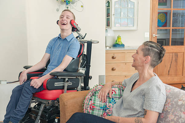 Happy cerebral palsy patient with his mom Color image of a real life young physically impaired cerebral palsy patient spending time with his mother at home. He is happy. amyotrophic lateral sclerosis stock pictures, royalty-free photos & images