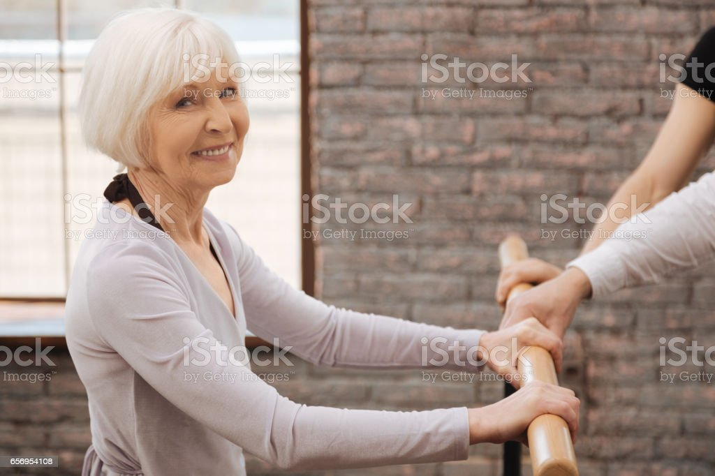 Happy charming pensioner dancing in the dance studio stock photo