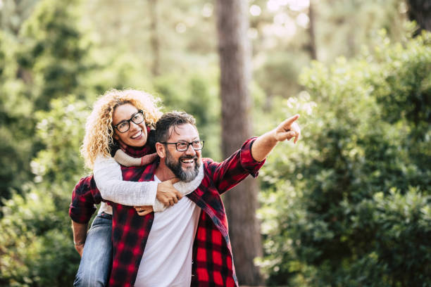 Happy cheerful adult beautiful couple have fun together and joy in the wood forest - concept of love and friendship with people - travel and environment  man and woman smiling stock photo