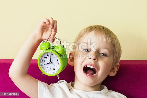 istock Happy cheerful boy holding an alarm clock, baby alarm clock 637648506