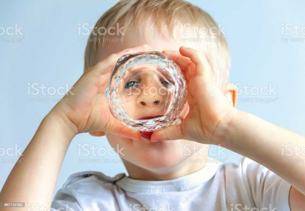 Happy cheerful boy is drinking from a glass, - foto stock