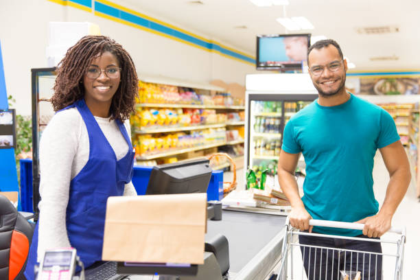Happy cheerful cashier and buyer posing at counter stock photo