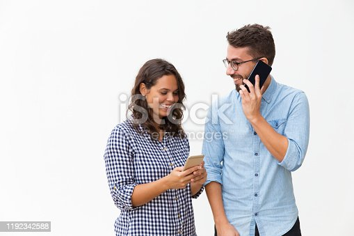 854381780 istock photo Happy cheerful couple calling on mobile phones 1192342588