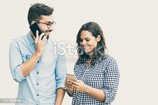 854381780 istock photo Happy cheerful couple calling on mobile phones 1217803466