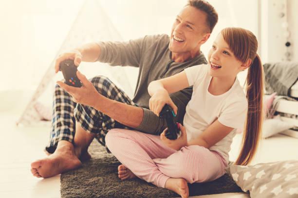 glücklich fröhliche mädchen spielen von videospielen - hochzeitsspiele eltern stock-fotos und bilder