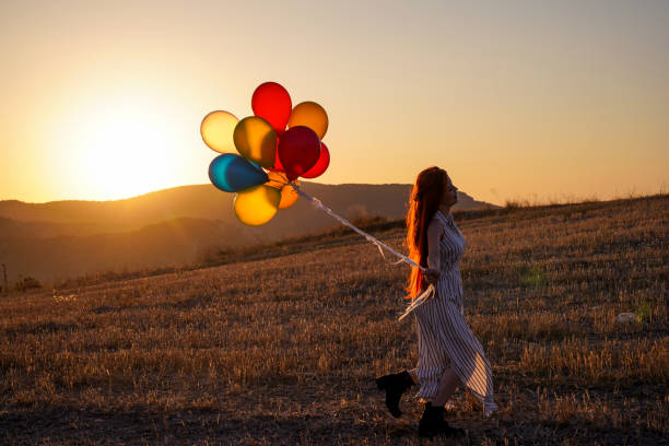 Happy cheerful girl with balloons running across meadow at sunset on nature in summer stock photo