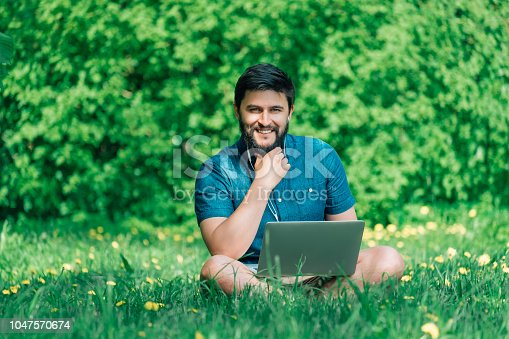 944992706 istock photo Happy cheerful hipster man with a laptop sitting outdoors on green grass. Freedom  concept 1047570674