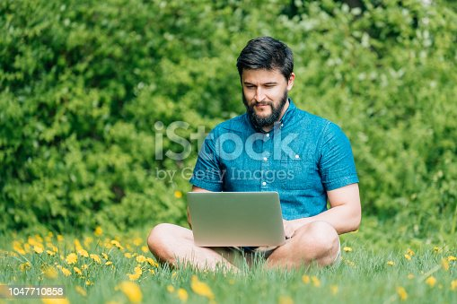 944992706 istock photo Happy cheerful hipster man with a laptop sitting outdoors on green grass. Freedom  concept 1047710858