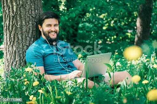 944992706 istock photo Happy cheerful hipster man with a laptop sitting outdoors on green grass. Freedom  concept 1047710960