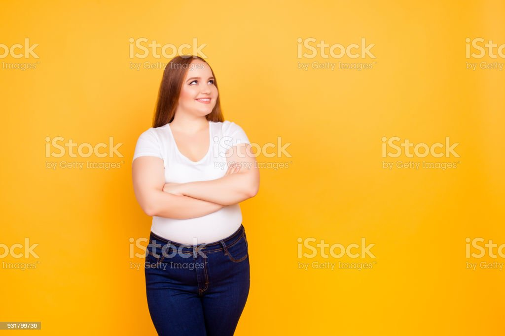 Happy cheerful joyful confident with chubby face oversize woman wearing casual tshirt and dark blue jeans, standing with folded arms, looking at empty blank space isolated on bright yellow background stock photo