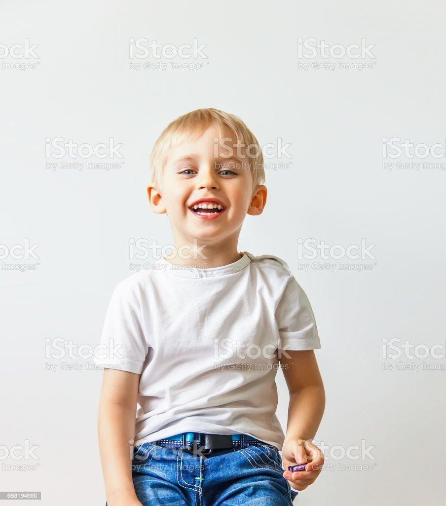快樂開朗的小男孩,玩笑在白色的背景下,軟焦點做鬼臉 免版稅 stock photo