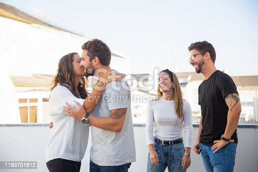 Happy cheerful old friends greeting and kissing each other on apartment terrace. Young men and women in casual meeting outside. Friends meeting or hangout concept