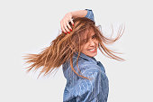 istock Happy cheerful woman playing with hair smiling and laughing, posing over white background. Beautiful happy female smiles broadly with healthy white teeth and blowing hair, isolated on white wall 1139022240