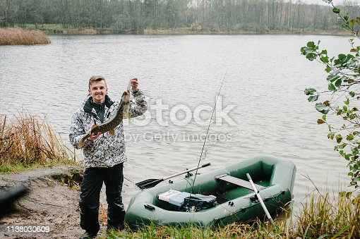 1145410808 istock photo Happy cheerful young fisherman hold a big fish pike near the boat on a background of lake and nature. Fishing background. Good catch. Trophy fish. angler. close up. 1138030609