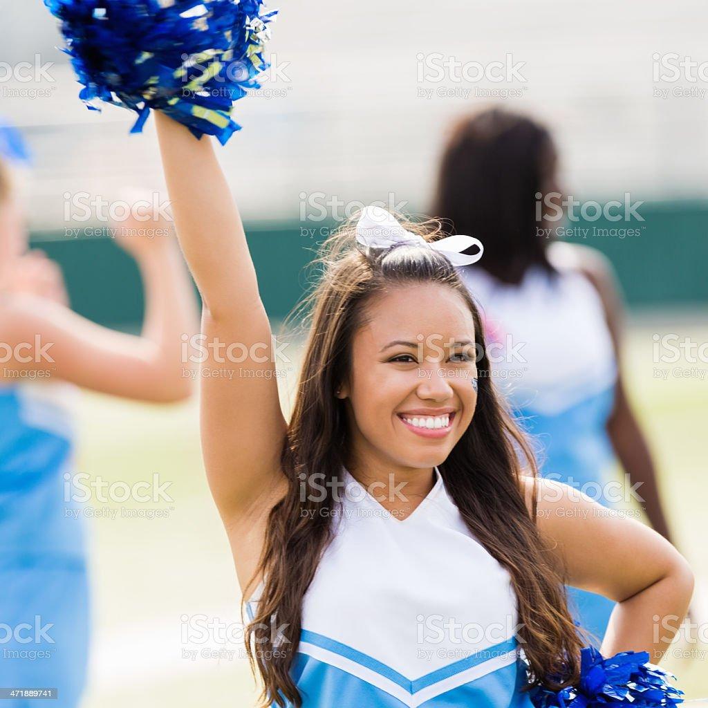happy cheerleader performing at high football game stock
