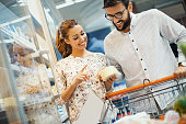 Young couple buying cheese at supermarket.