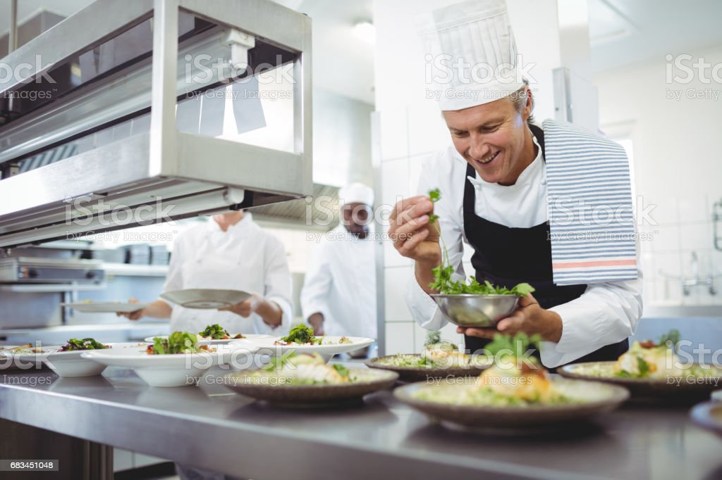 Happy chef garnishing appetizer plates at order station stock photo