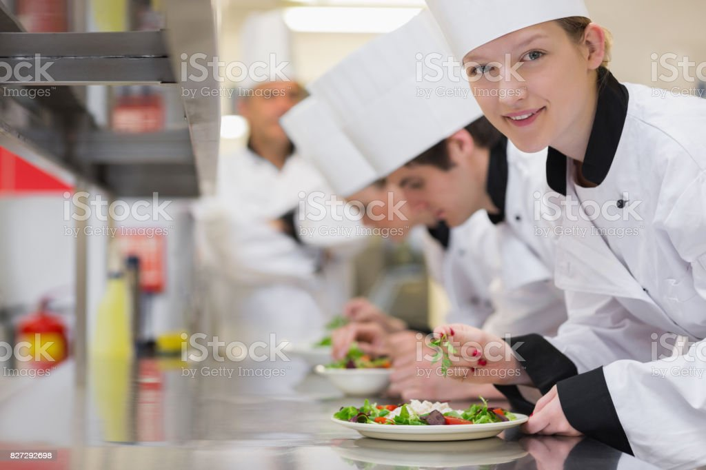 Happy chef looking up from preparing salad stock photo