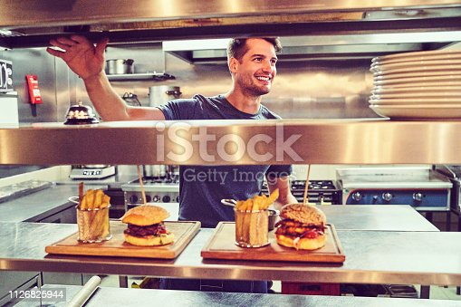 Happy chef with prepared orders waiting at counter. Man wearing casuals looking away. He is standing in commercial kitchen.