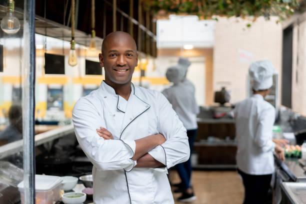 Glücklicher Koch, der in einer Küche in einem Restaurant arbeitet – Foto
