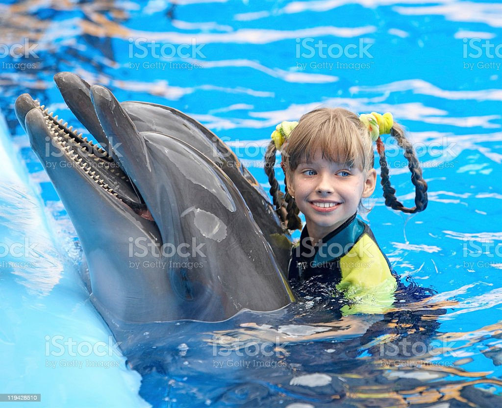 Happy child and dolphin in blue water. stock photo
