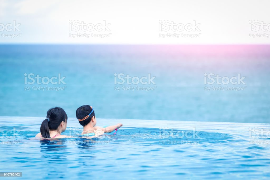 Happy child and mother in swimming pool stock photo