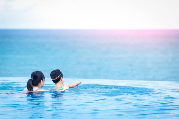 glückliches kind und mutter im schwimmbad - ferienhaus thailand stock-fotos und bilder