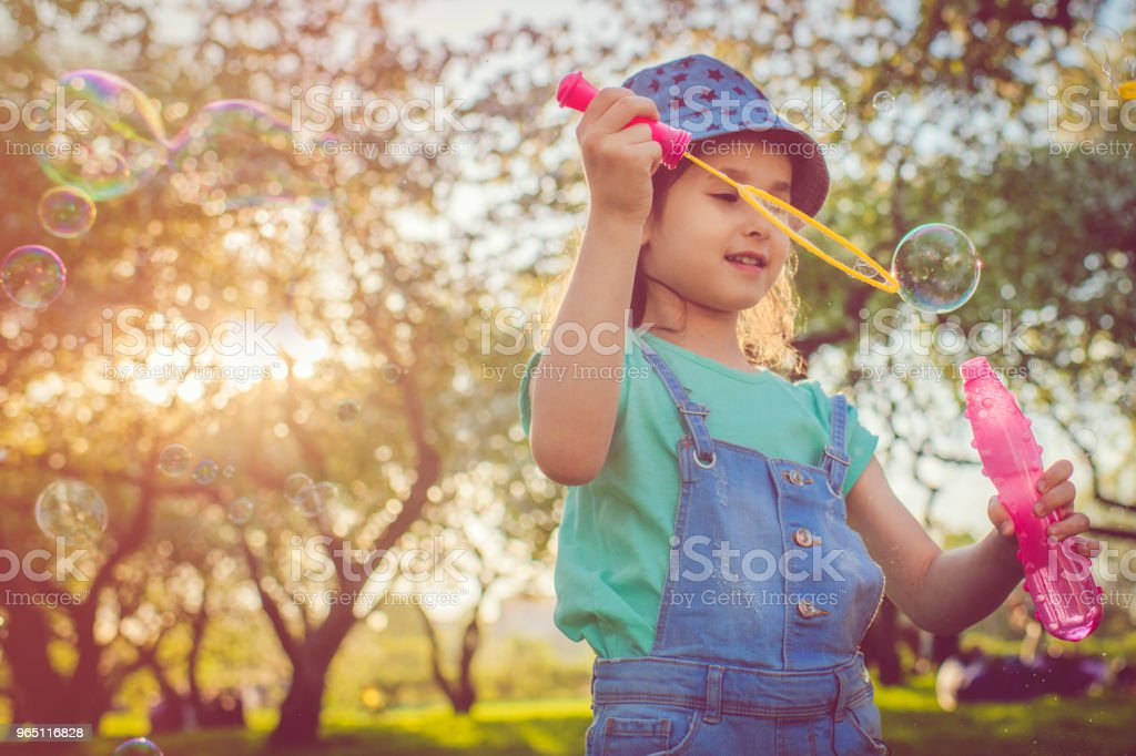 Happy child blowing bubbles in the park zbiór zdjęć royalty-free