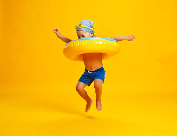happy child boy in swimsuit with swimming ring donut on colored yellow background - summer background стоковые фото и изображения