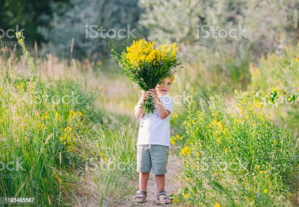 Photo of Happy child boy with bouquet of wild flowers in his hands enjoying for mother.