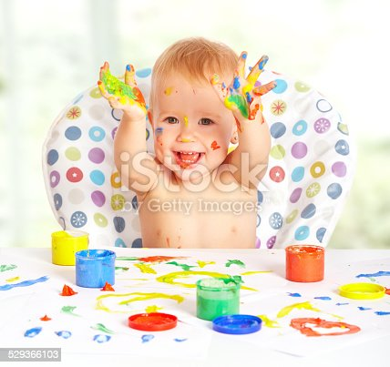 istock happy child draws with colored paints hands 529366103