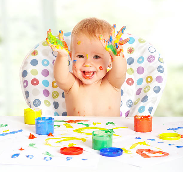 glückliches kind lockt mit bunten farben hände - lustige babybilder stock-fotos und bilder