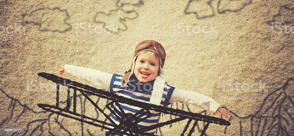Happy child dreams of becoming a pilot aviator and plays stock photo