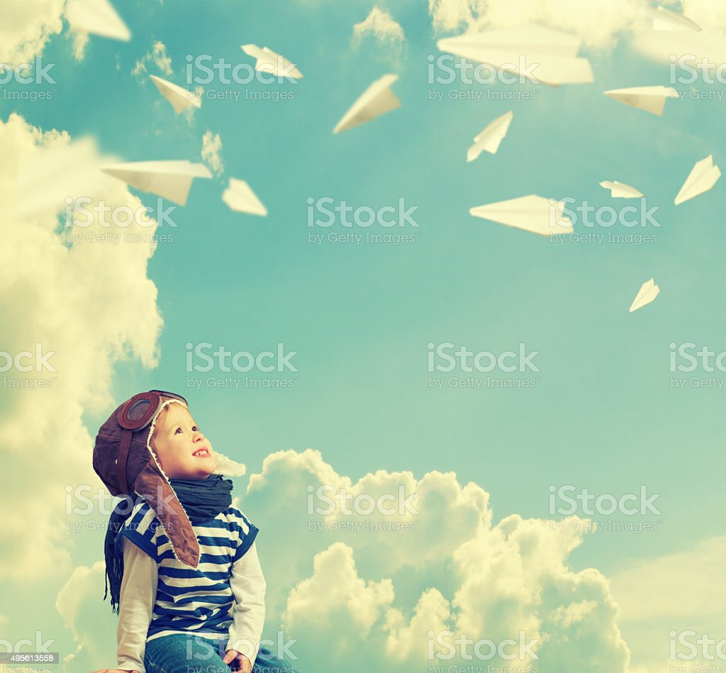 Happy child dreams of becoming pilot aviato, plays with plan stock photo