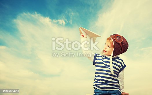 istock Happy child dreams of becoming pilot aviator,  plays with plan 495613420