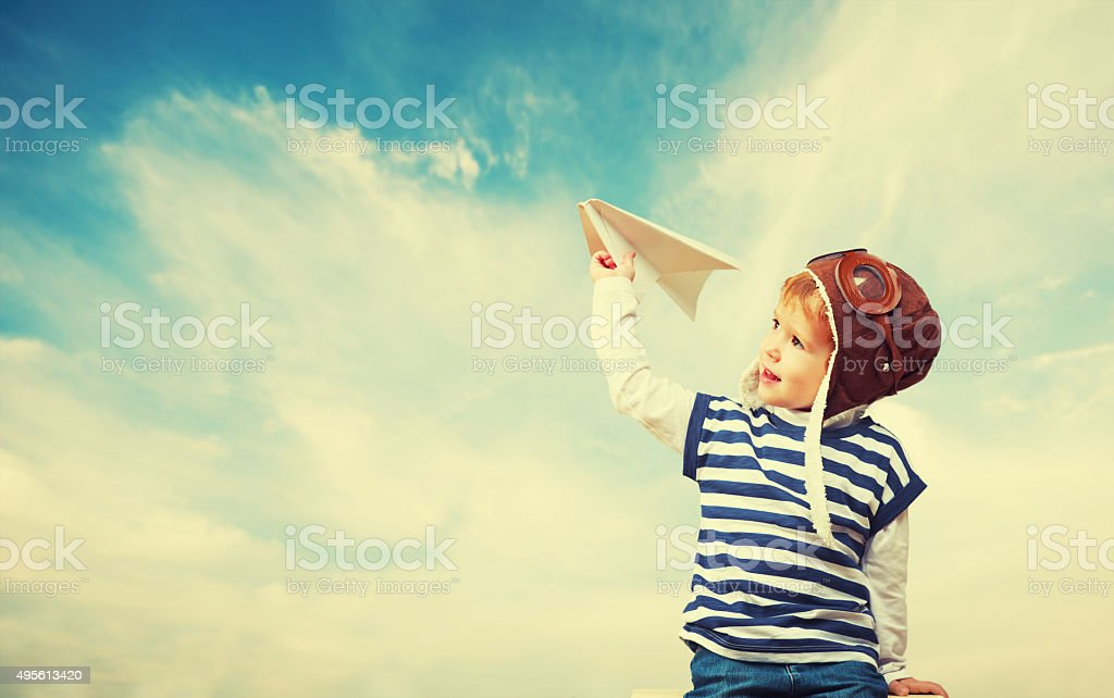 Happy child dreams of becoming pilot aviator,  plays with plan stock photo