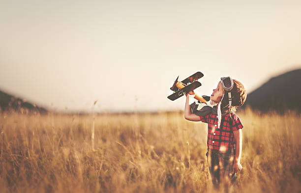 happy child dreams of traveling and playing with an airplane - enfant aviateur photos et images de collection