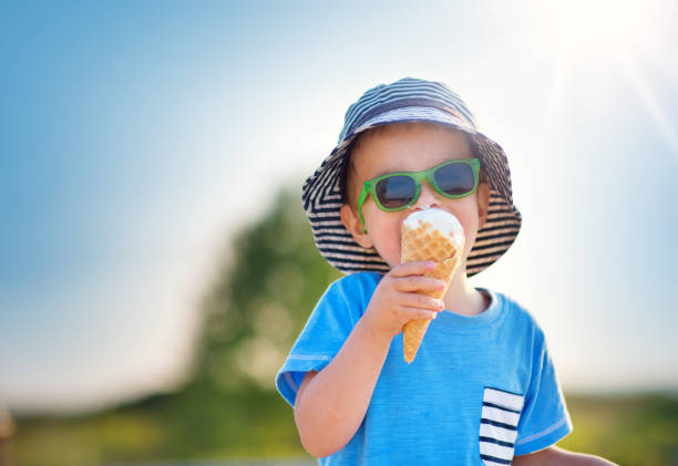 happy child eating ice cream outdoors in summer - summer stock pictures, royalty-free photos & images