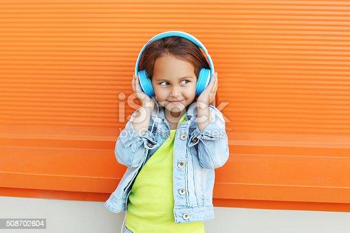 istock Happy child enjoys listens to music in headphones over orange 508702604