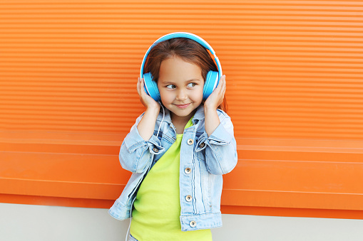 istock Happy child enjoys listens to music in headphones over orange 508702604