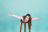 Happy child flying on chair, fashion. Small girl with long brunette hair smile, . Fashion, casual style. Beauty, look, hairstyle. Energy, activity, sport, punchy pastel trend