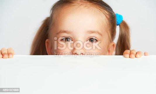 519837800 istock photo Happy child girl and blank white poster billboard 489492666